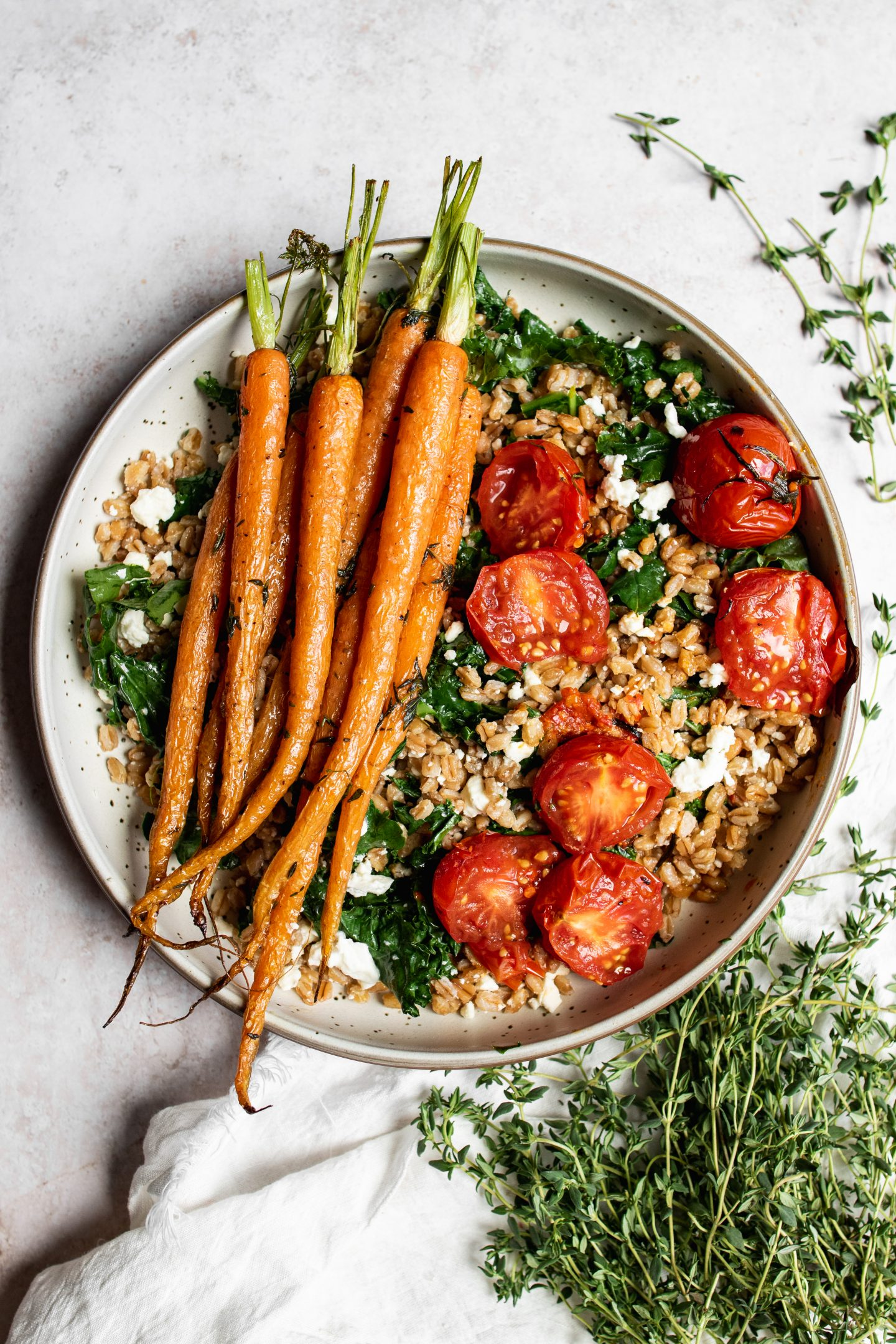 Composed farro bowl with kale, tomatoes, and roasted carrots