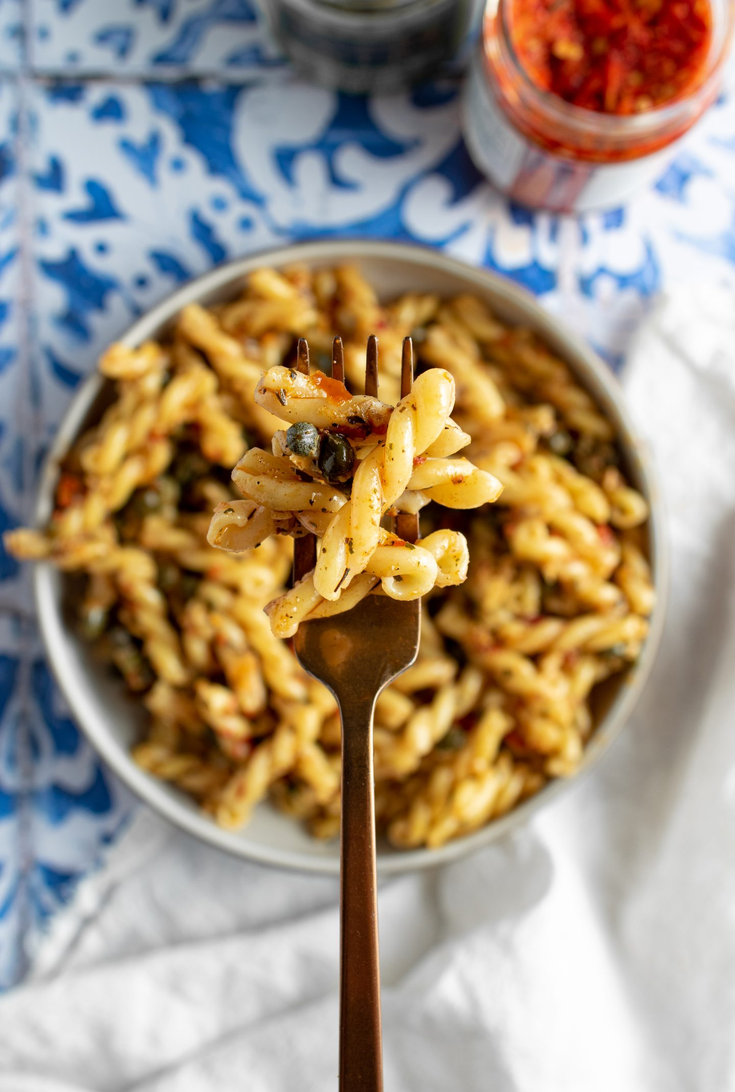 spicy caper pasta on a fork