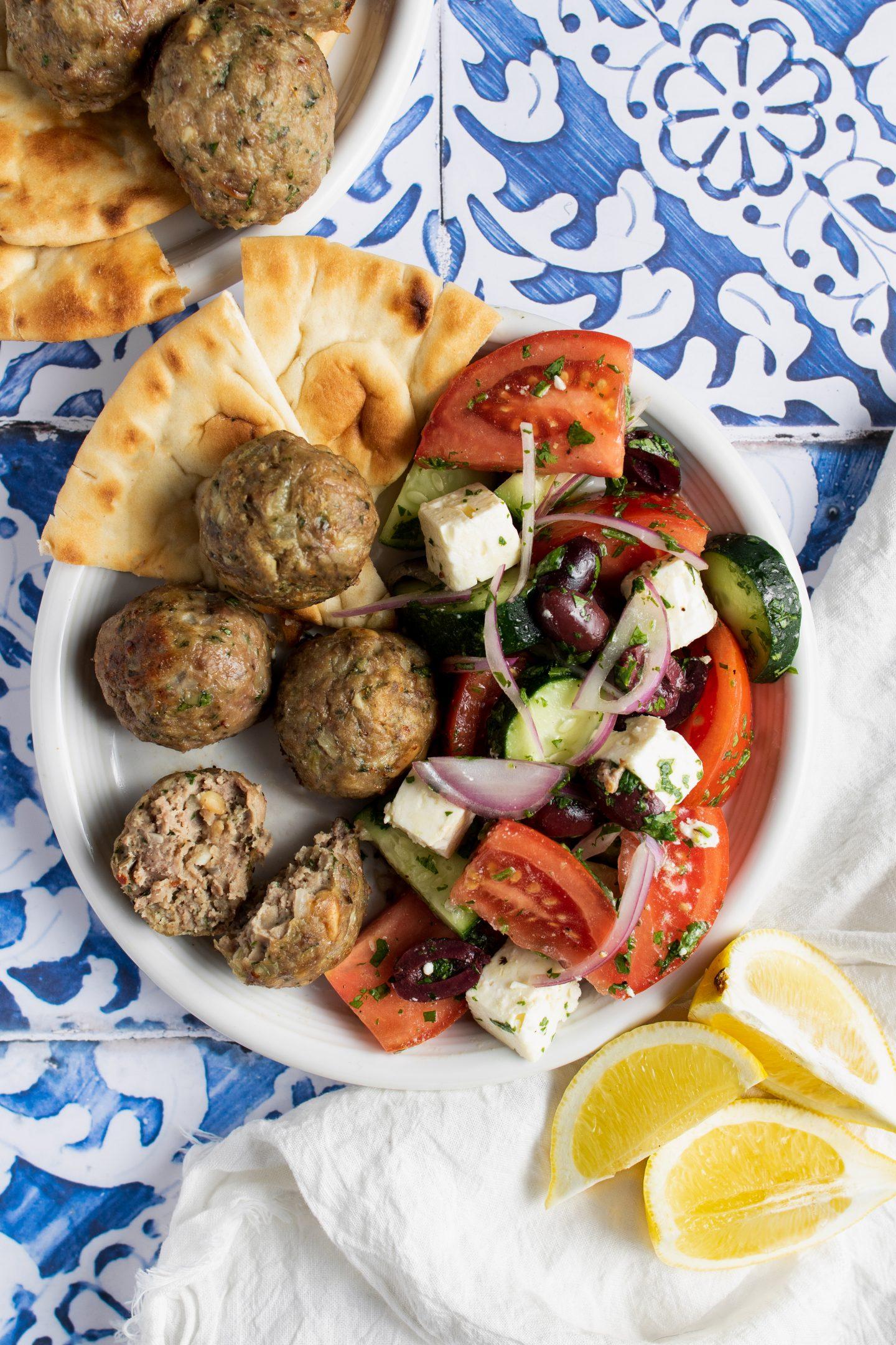 plate of greek lamb meatballs on the side of a greek salad