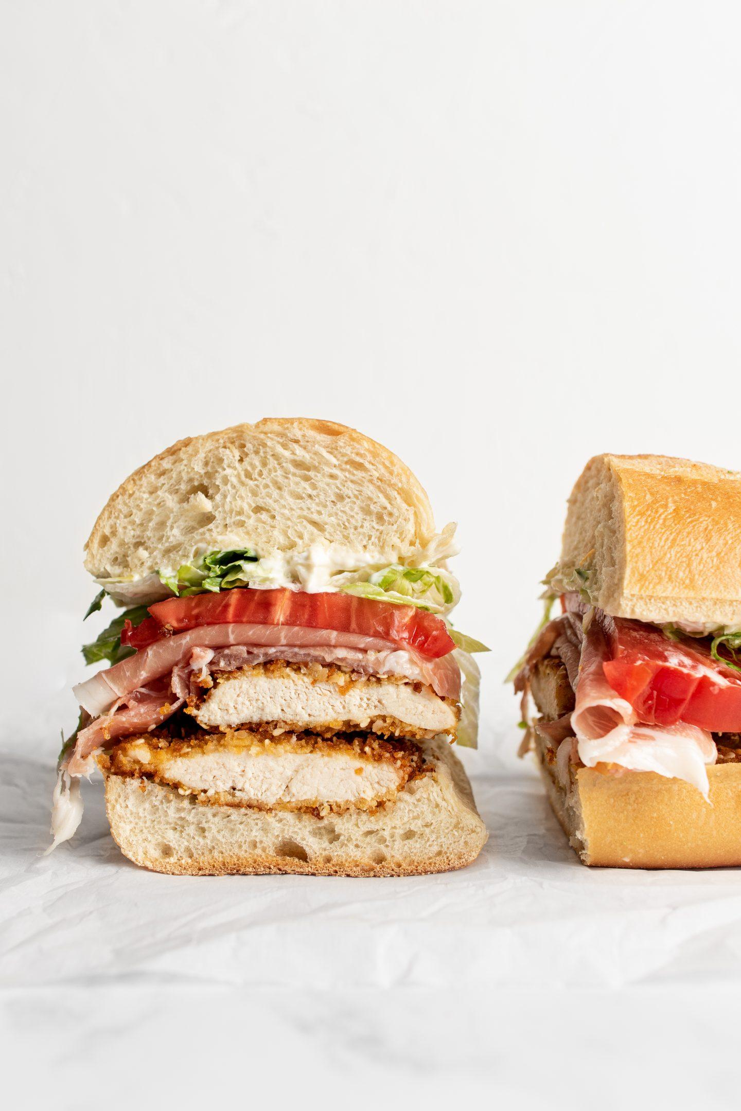 crispy sesame chicken sandwich with prosciutto, lettuce, tomato, and mayo